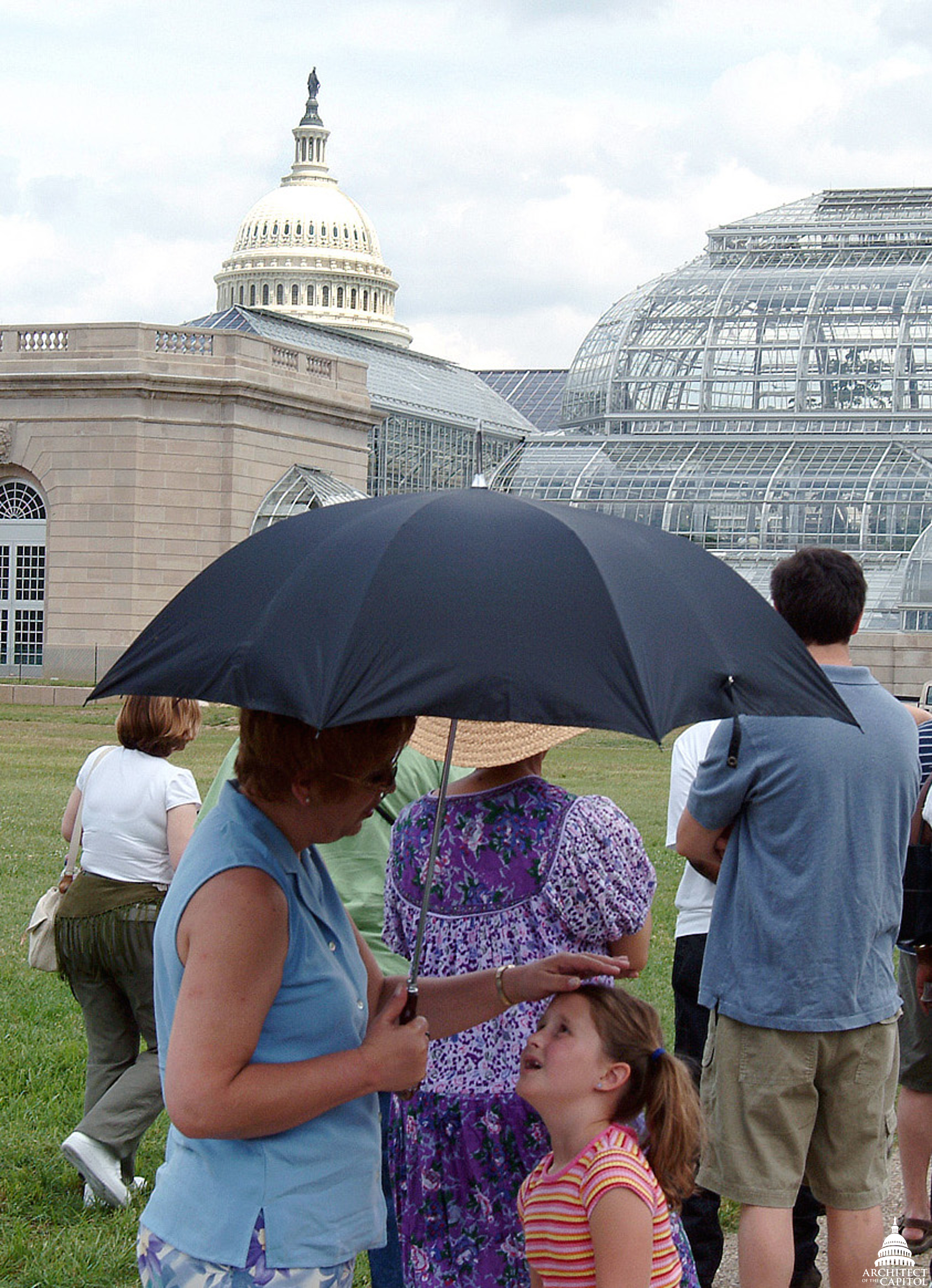 Visitors shade themselves from the summer sun with an umbrella.