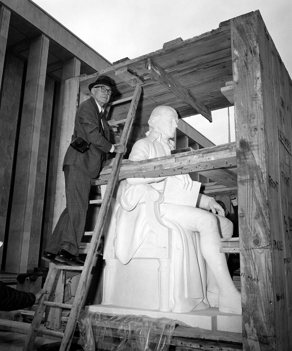 Sculptor Walker Hancock examines the James Madison statue when it was delivered in 1976. The sculpture is carved of Carrara marble.