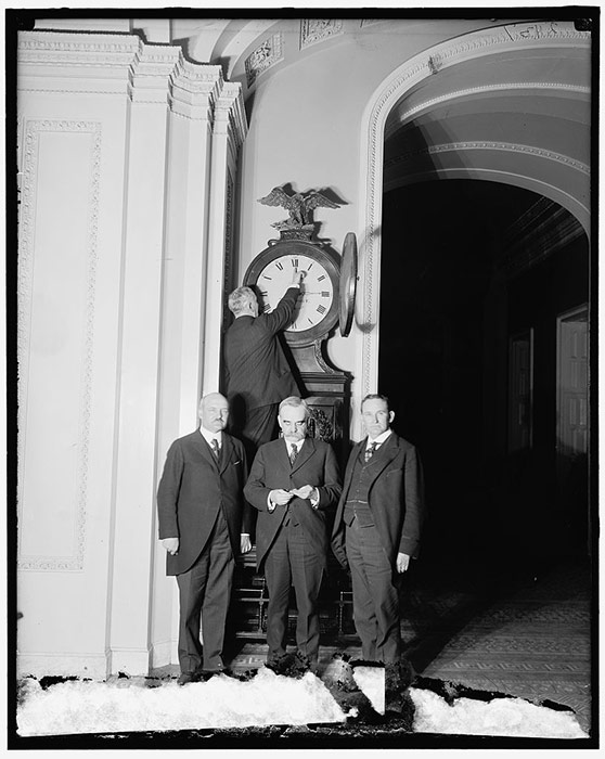 Senate Sergeant at Arms Charles Higgins turns forward the Ohio Clock for the first Daylight Saving Time, 1918.