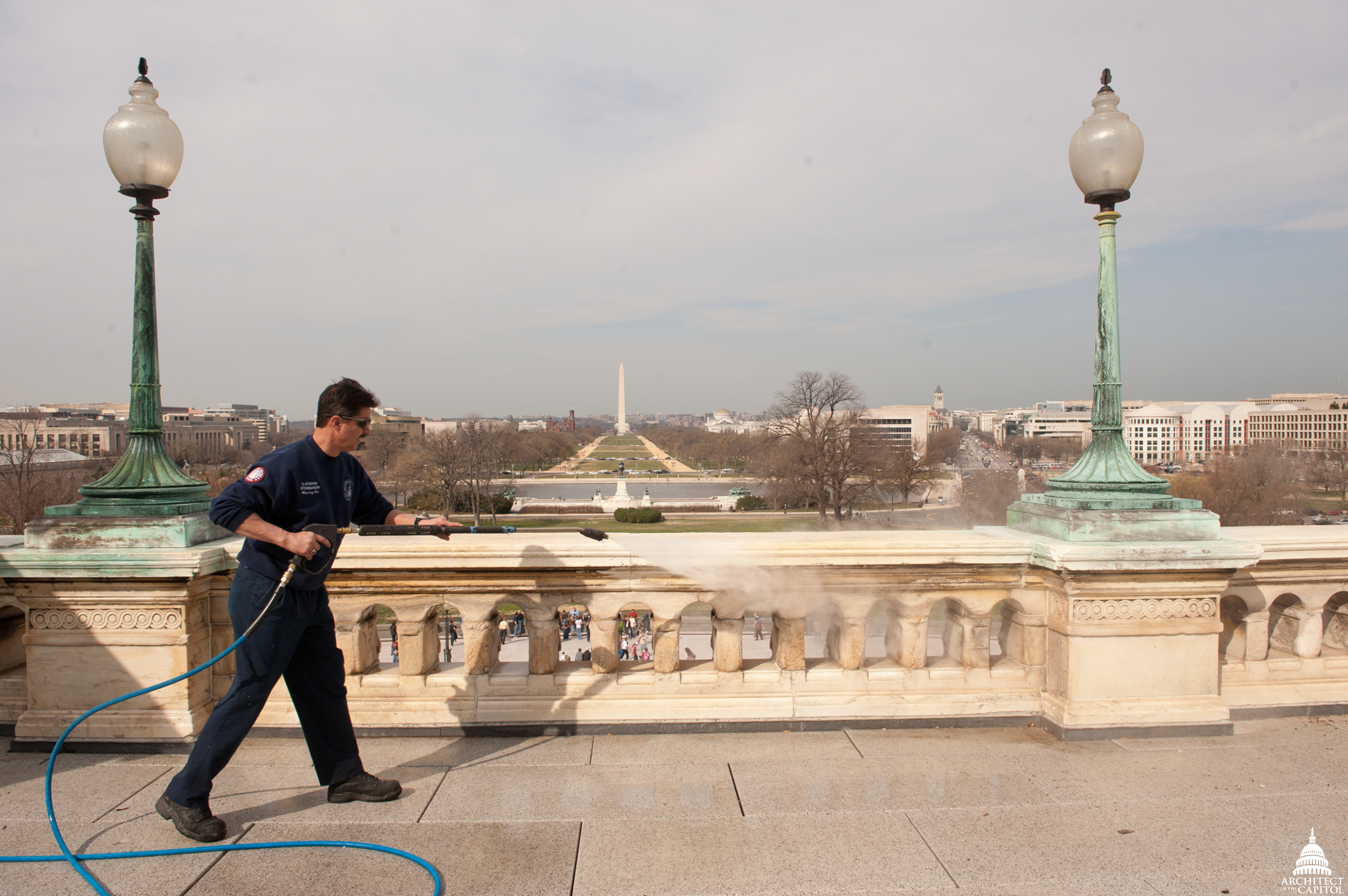 A stonemason power washes the upper west terrace of the U.S. Capitol.