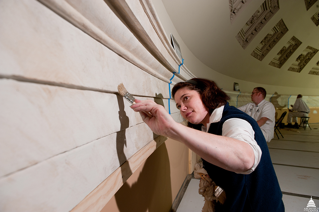 Claire Sharp, AOC Capitol decorative painter, helps restore the Old Senate Chamber using a faux marbleizing technique.