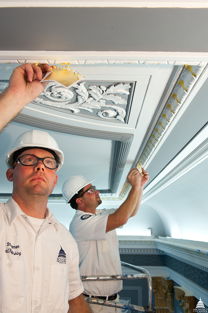 Timothy Steadman and Charles Taylor, AOC Senate painters, carefully apply gold leafing within a Senate Committee room.