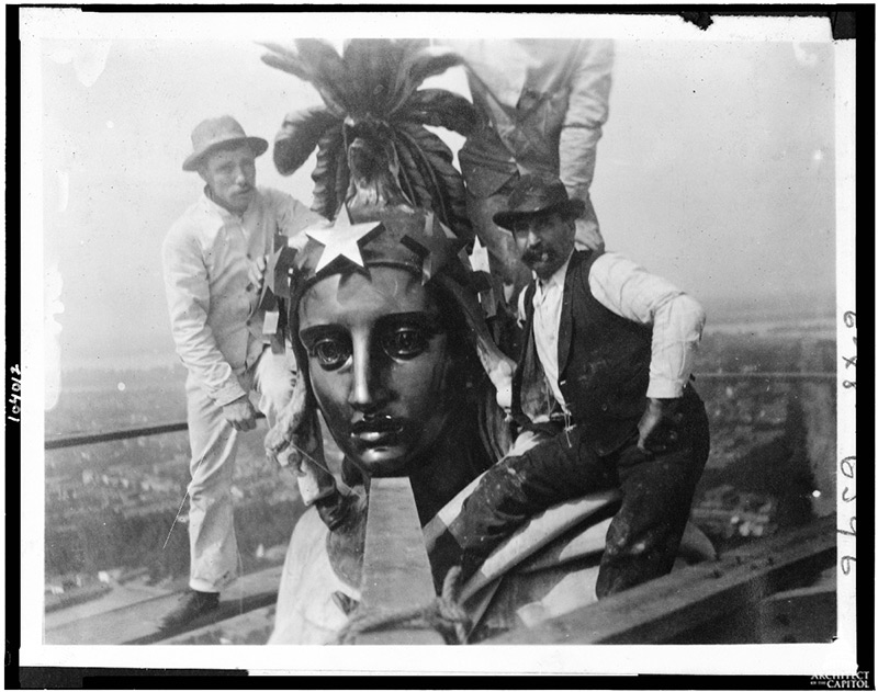 "AOC employees take a ""selfie"" (note string in hand of individual all in white) atop the Statue of Freedom in 1913."