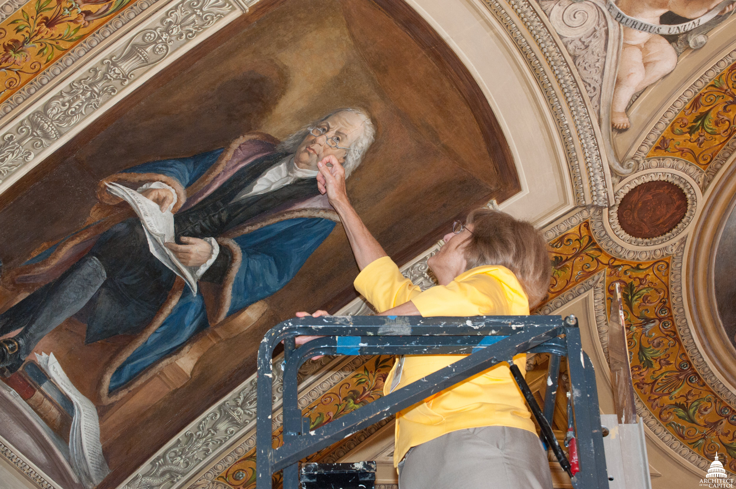 Dr. Barbara Wolanin examines a painting of Benjamin Franklin.