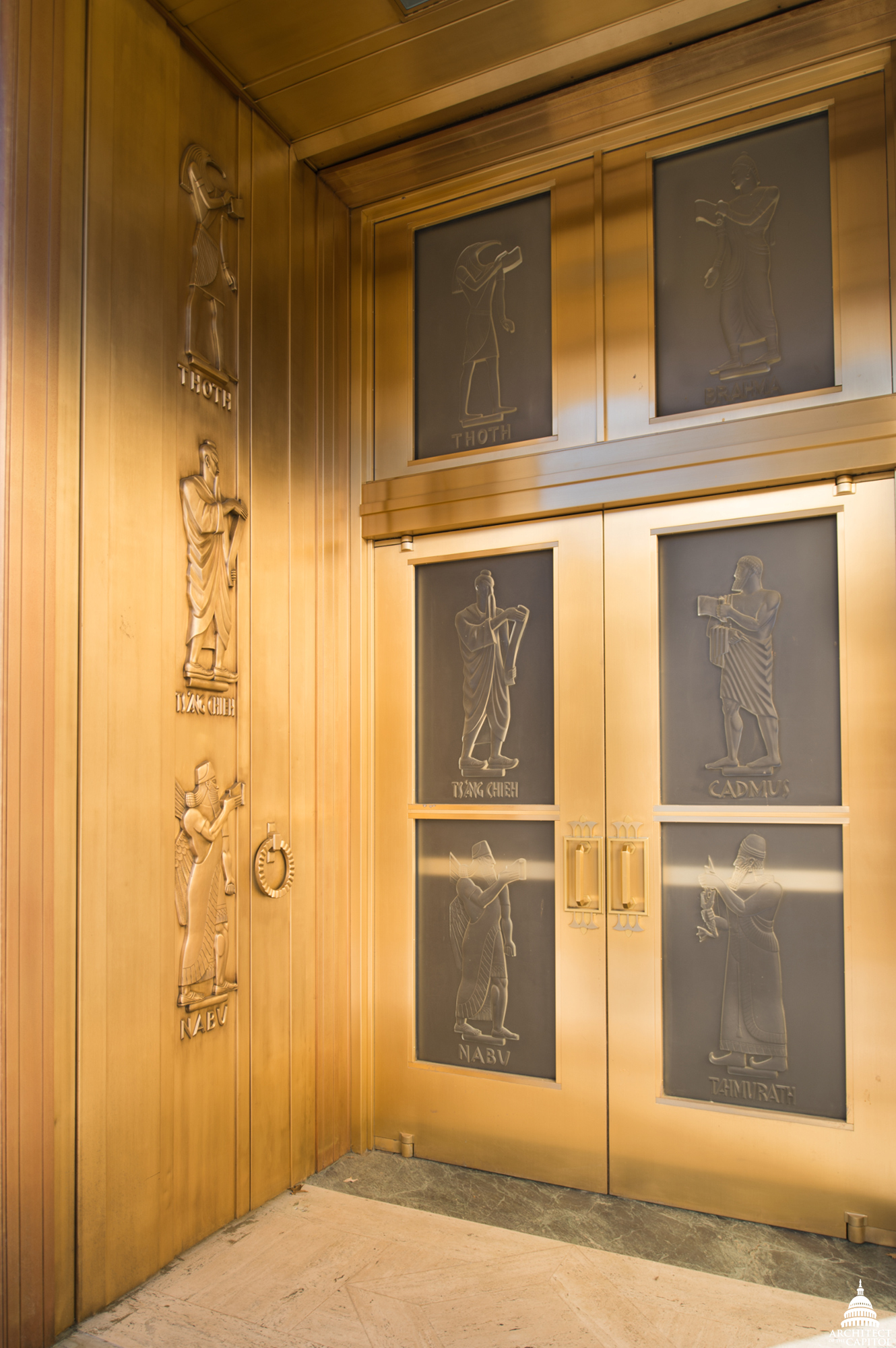 The bronze and glass doors of the John Adams Building.