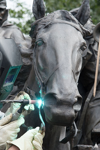 Welding of bronze work to a horse sculpture at the Grant Memorial during restoration in 2016.
