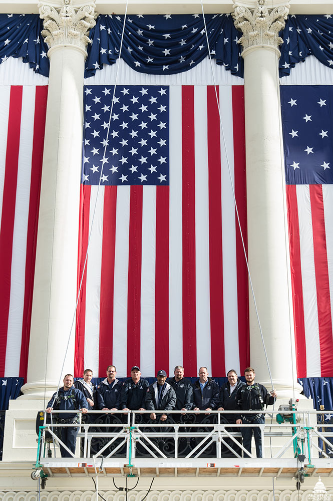 AOC employees in front of a flag near the inaugural platform on the U.S. Capitol's West Front.