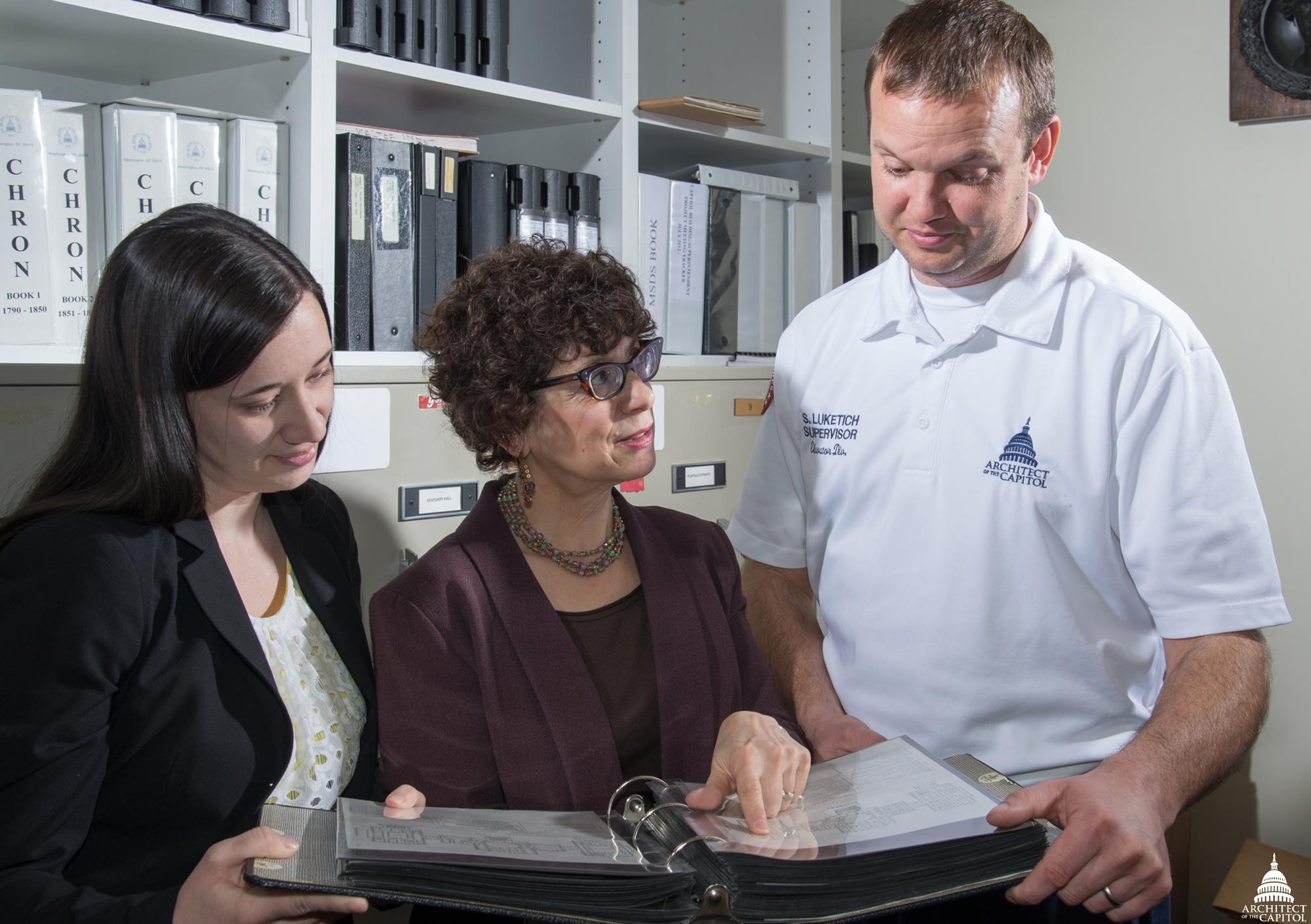 AOC's Erin Nelson, Michele Cohen and Scott Luketich review old floor plans.