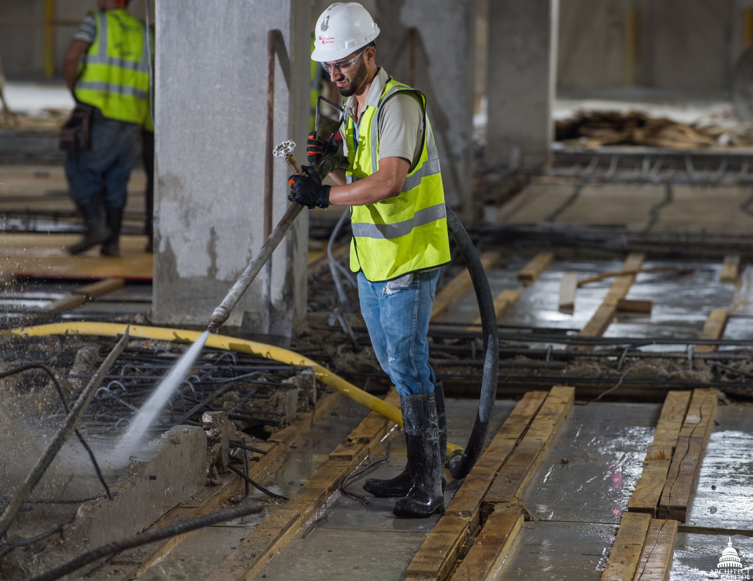 A construction worker in the Rayburn Garage uses high pressure water to clean off the beam and rebar to prep them for the new concrete slab and beam encasement.