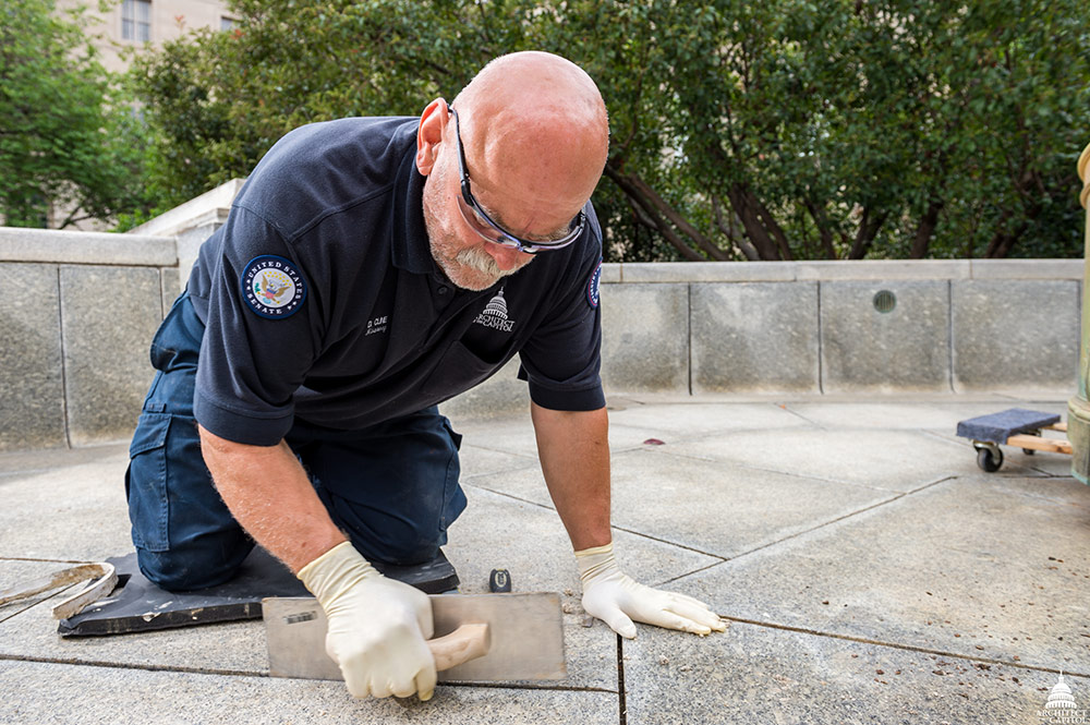 Donald Kline removes failing caulking from the Russell Courtyard fountain.