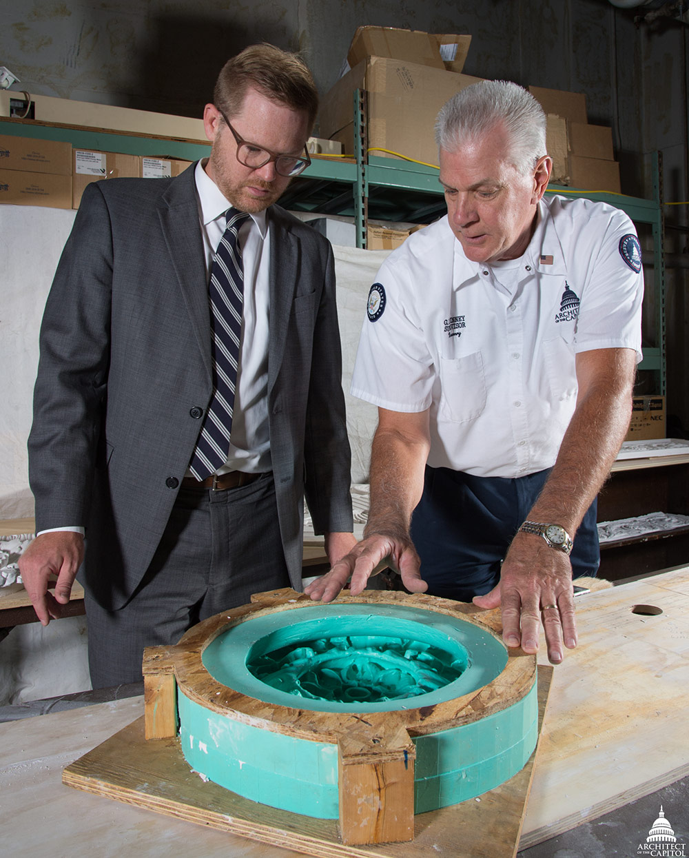 Assistant Superintendent for Tenant Services Paul Kirkpatrick learns more about the mold making process from Senate Masonry Branch Supervisor Glenn DeVinney, who has been with the Architect of the Capitol for 20 years.