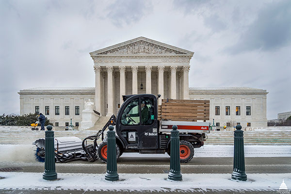 Members of the Architect of the Capitol team clear snow in front of the Supreme Court Building.