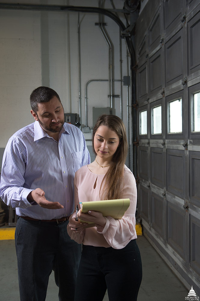 AOC Supply Management Officer Paul Venturella reviews records with intern Mary Delaney.