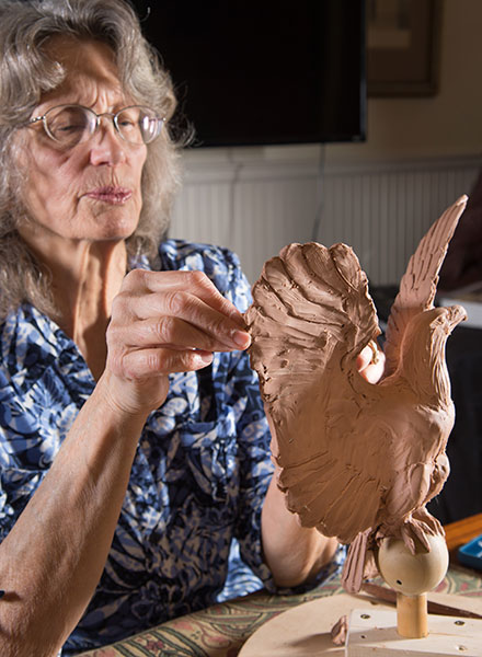 An artist creates a clay model of an eagle to go atop a light post at the Grant Memorial.