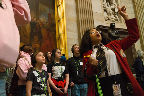 A visitor guide shows a tour group through the U.S. Capitol Rotunda.