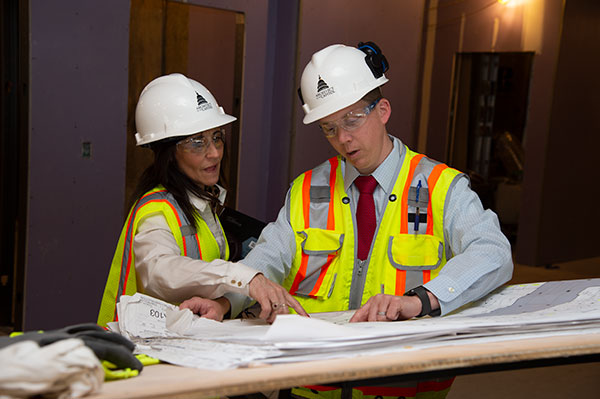 Two AOC engineers review building plans for the U.S. Capitol campus.