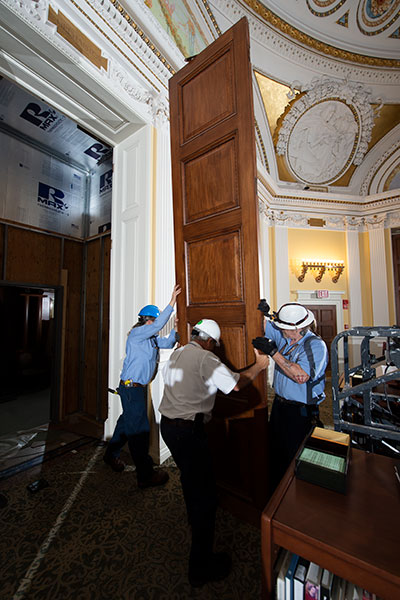 Carefully removing a 120-year-old historic door at the Thomas Jefferson Building, weighing upwards of 275 pounds.