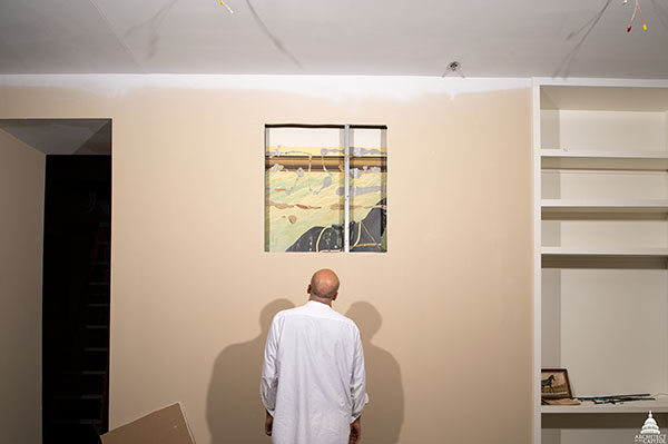 An AOC painter examines the Blackjack painting uncovered during a recent renovation.
