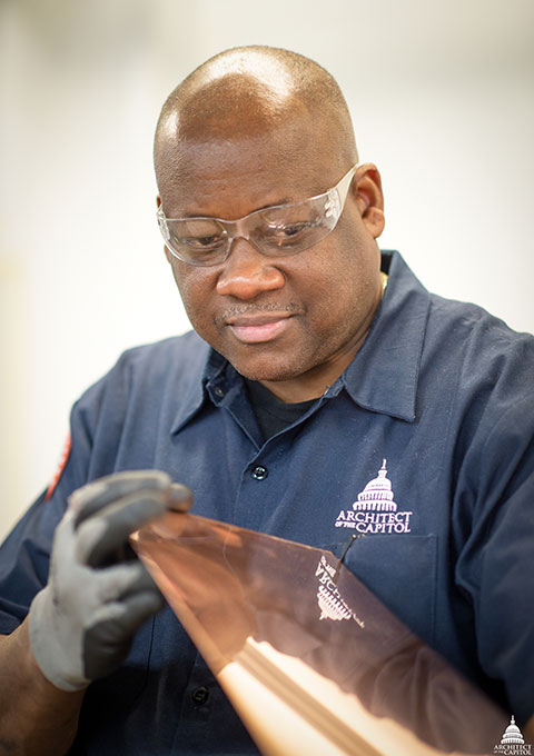 A member of the AOC's Capitol Building Sheet Metal Shop examines a piece of metal.