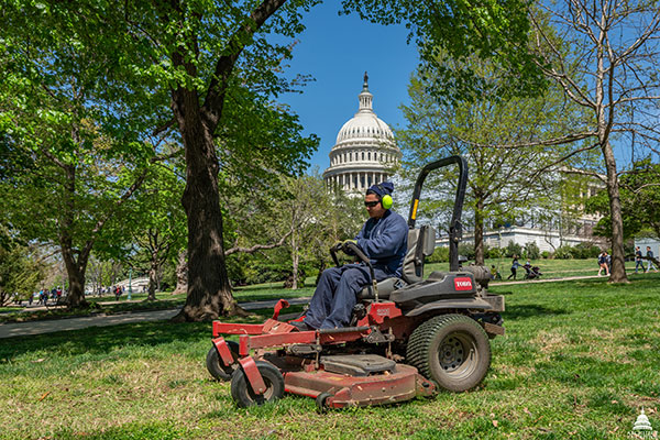 An AOC employee mows the lawn at the U.S. Capitol.