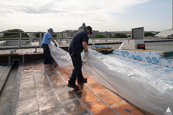 Members of the AOC Sheet Metal Shop cover the newly placed copper with plastic sheeting at the end of their shift.