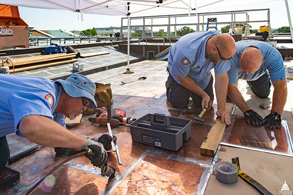 Members of AOC's Sheet Metal Shop solder and install flat seam copper roof panels.