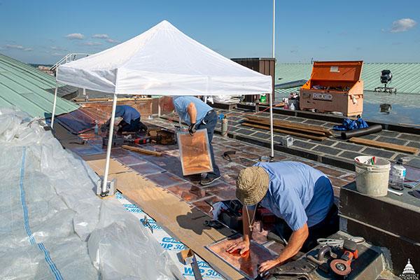Members of the AOC Sheet Metal Shop install flat seam copper roof panels.