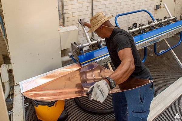 An AOC Sheet Metal Mechanic bends a copper wall flashing.