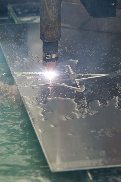 Sparks fly as the plasma torch cuts a star out of an aluminum sheet.