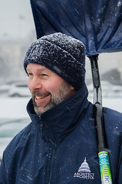 A member of the Architect of the Capitol team removed snow with a smile.