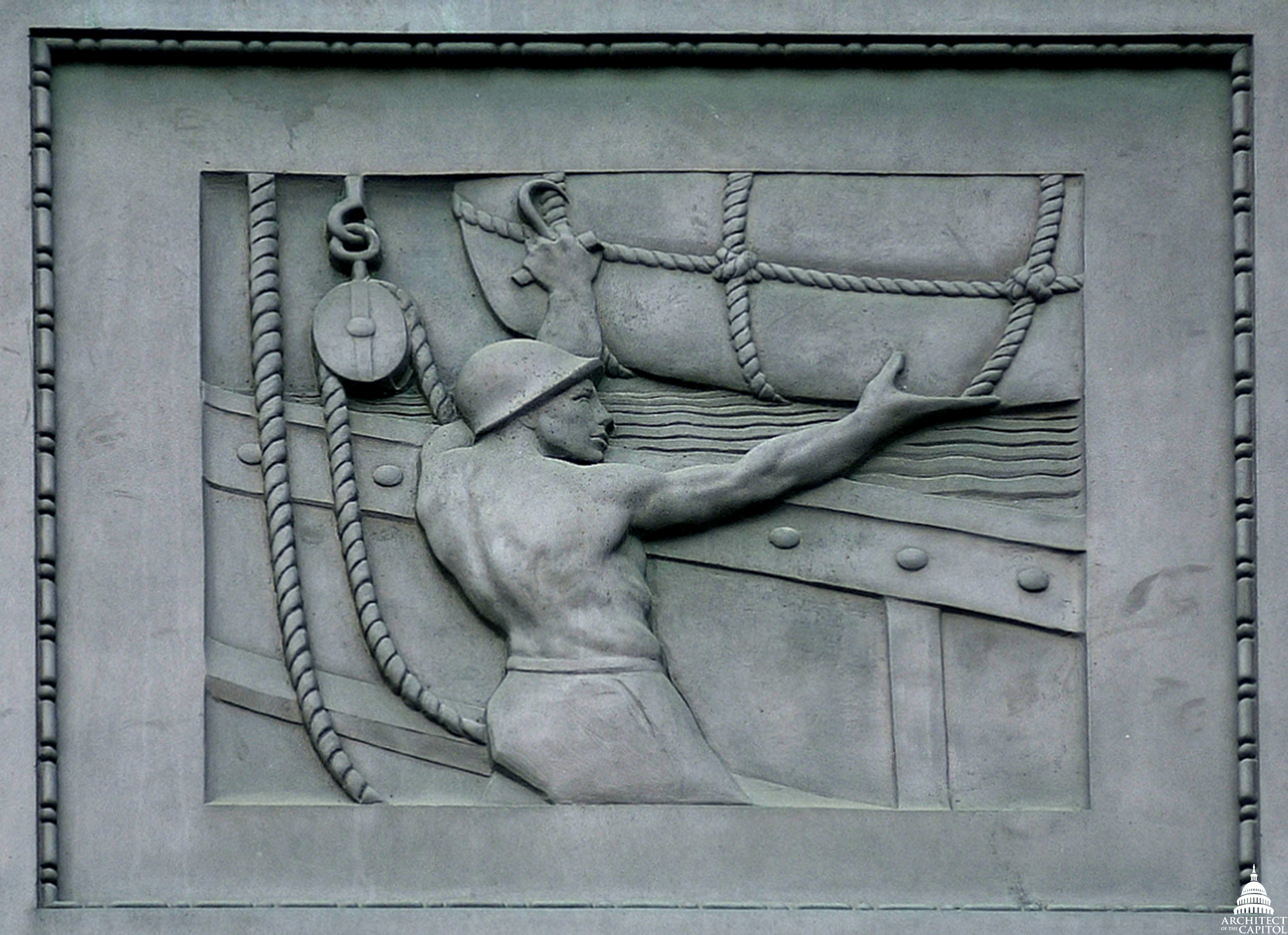A sailor maneuvers cargo in a panel on exterior of the Dirksen Senate Office Building.