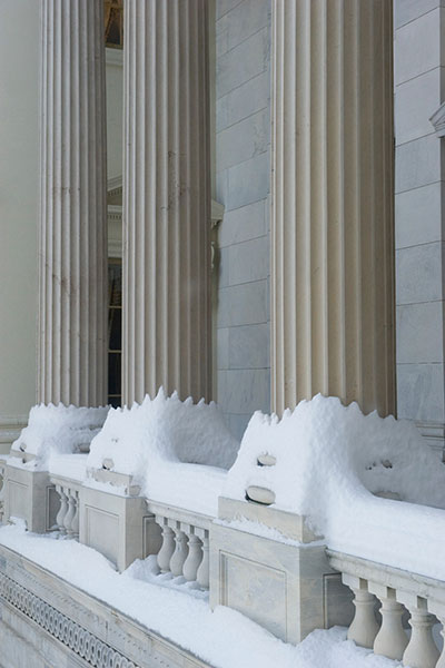 Columns of the U.S. Capitol covered in snow.