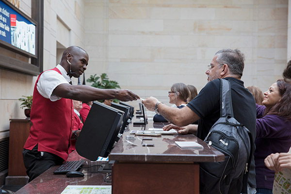 A visitor assistant hands a guest their tour badge at the U.S. Capitol Visitor Center info desk.