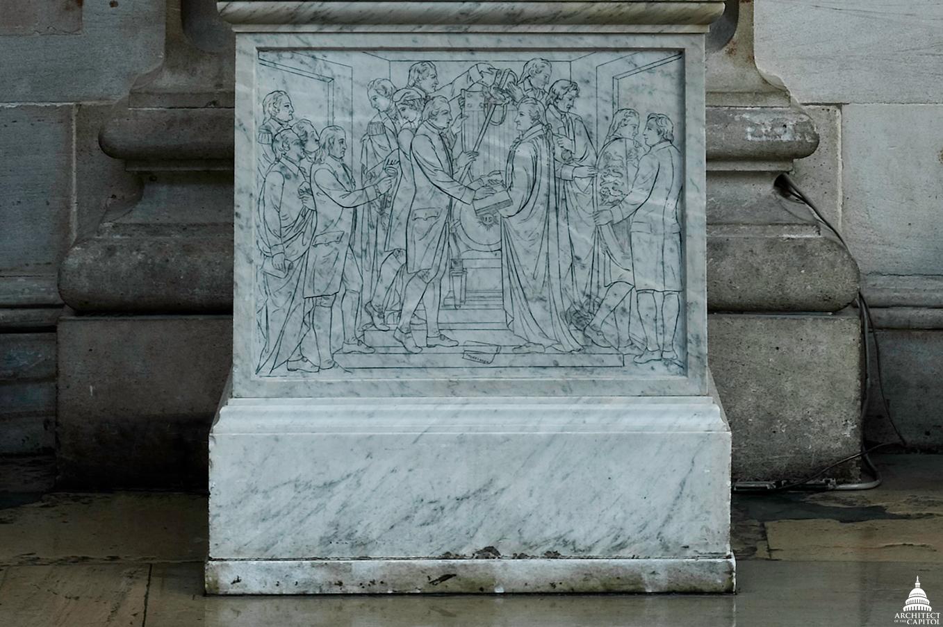 Alexander Hamilton's statue features a unique pedestal depicting the inauguration of George Washington.