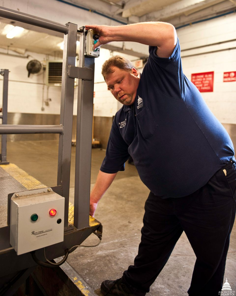 Industrial Mechanic Equipment Leader Brian Bradley tests the pressure switch on the loading dock leveler in the Rayburn Building.