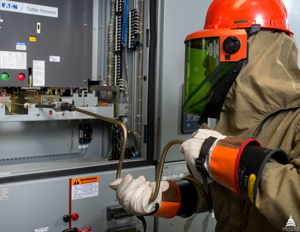High-voltage electrician Da'suan Mason follows precise procedures and wears a fireproof 40 cal arc flash suit while performing regular preventive maintenance on a 15,000 volt circuit.