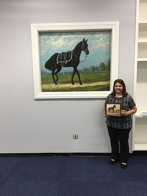 Former AOC employee Karen Livingston poses with the Blackjack painting while holding the painting it was based on.