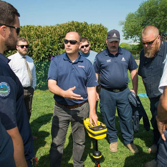 AOC employees test an underground utility locator on the West Front lawn of the U.S. Capitol.