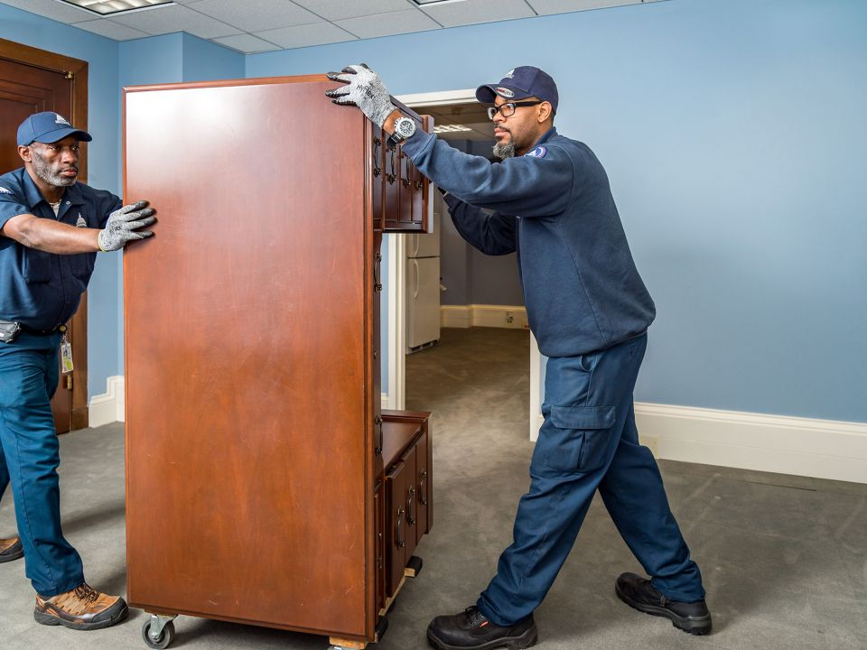 AOC employees moving furniture in a Senate office building.