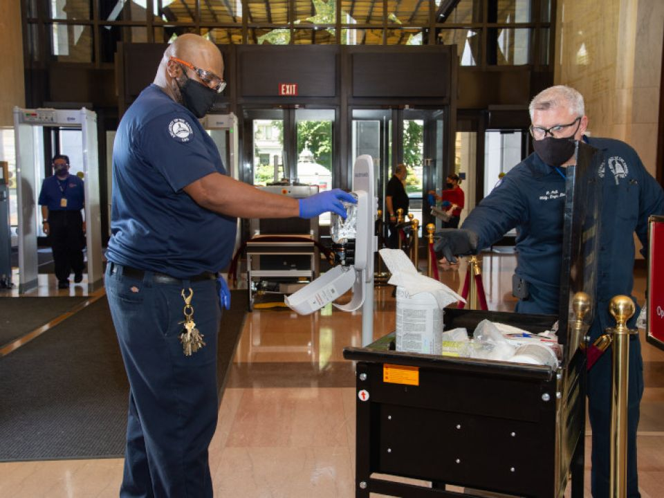Robert Hollins and Roger Hall clean high-touch surface areas and work spaces in the Library of Congress buildings.