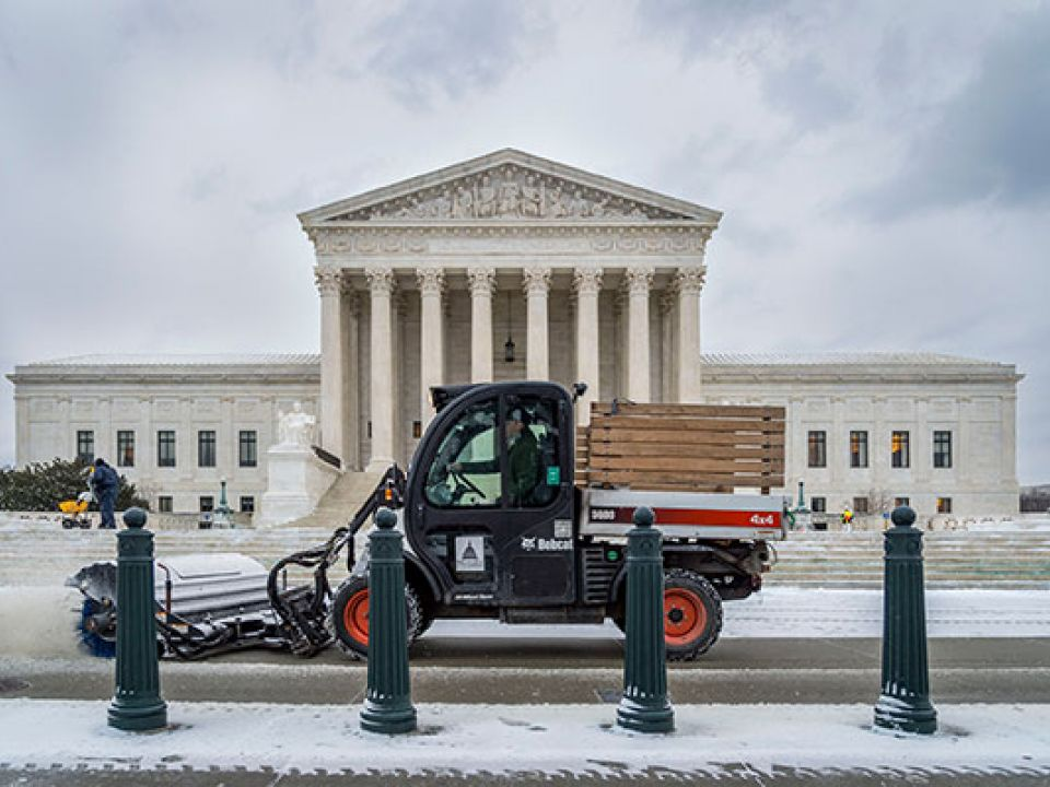 A member of the U.S. Capitol Grounds and Arboretum team clears snow in front of the Supreme Court Building.