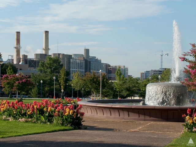 Fountain and landscaping with a view of the Capitol Power Plant from a distance.