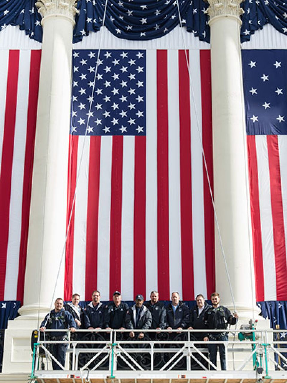 Employees of the Architect of the Capitol pause to stand in front of a flag during inauguration set up.